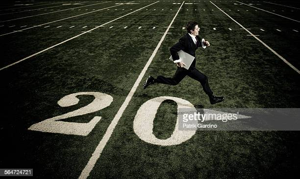 Businessman with Laptop Running on Football Field