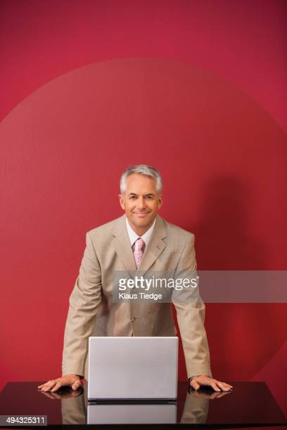 Businessman with laptop standing at conference table