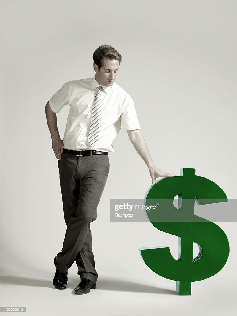 Businessman with large dollar symbol : Stock-Foto