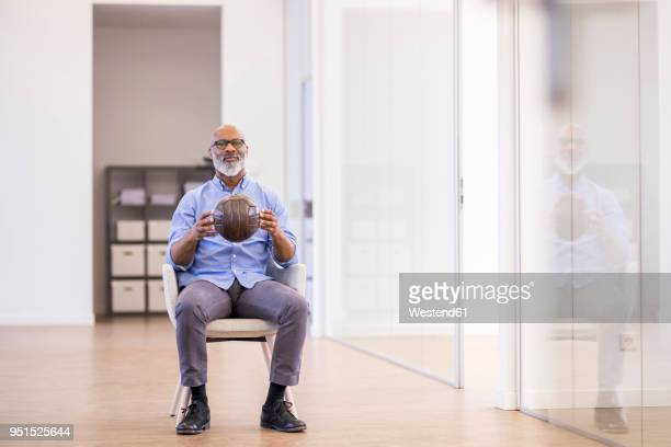 Businessman with leather ball sitting on arm chair in the office