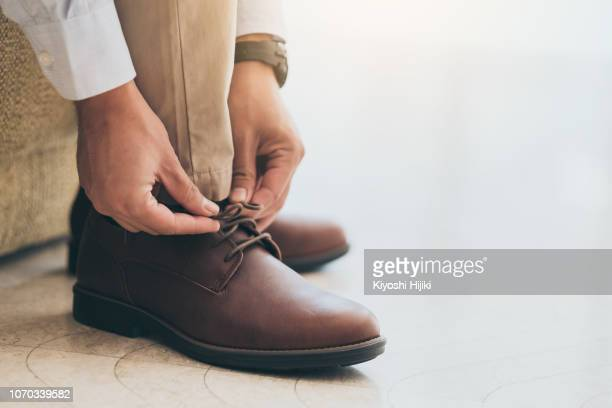 businessman with leather shoes tying shoe laces - brown shoe stock pictures, royalty-free photos & images