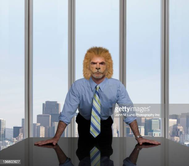 businessman with lion's head leaning on table - lion feline stock pictures, royalty-free photos & images