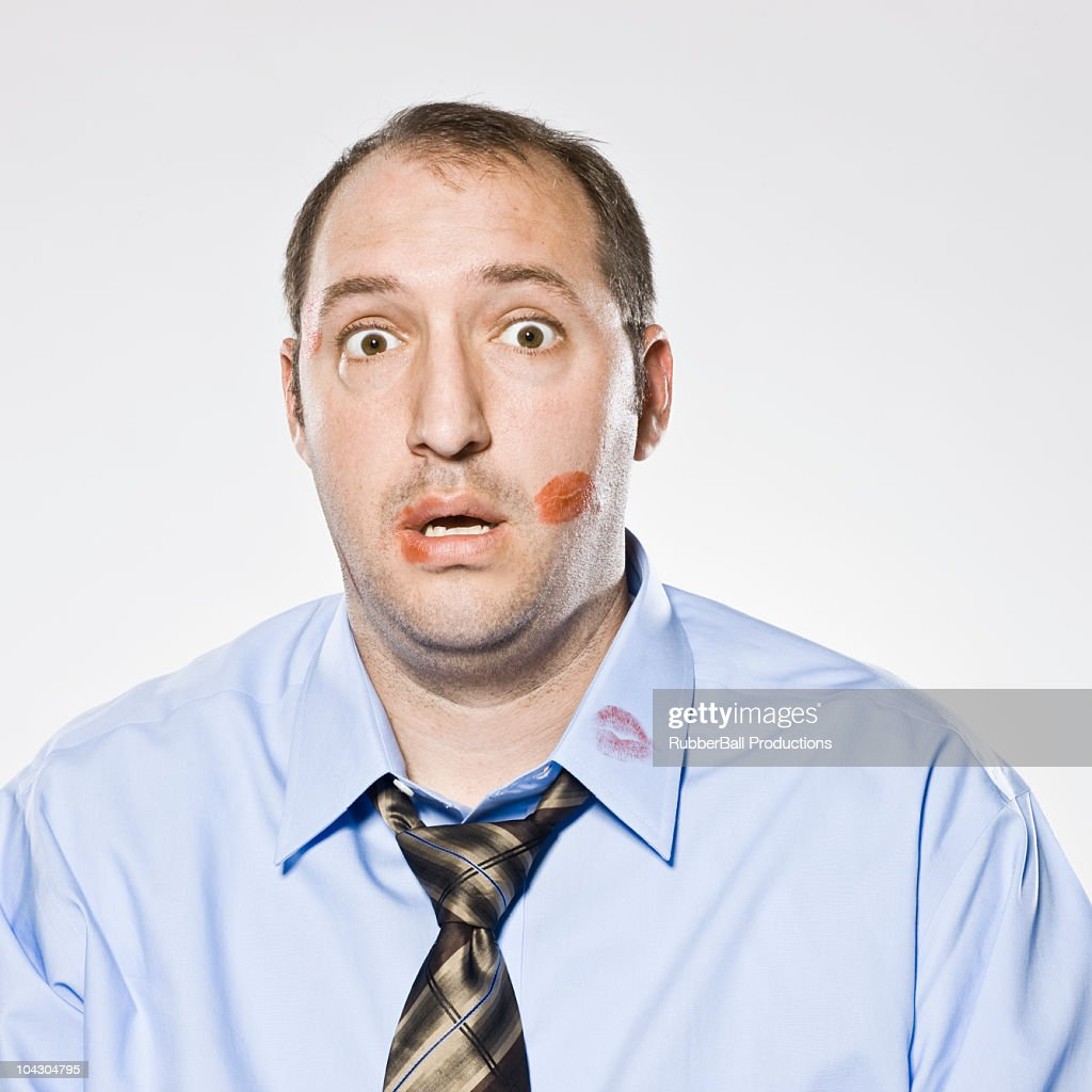 businessman with lipstick kiss marks all over his face : Stock Photo