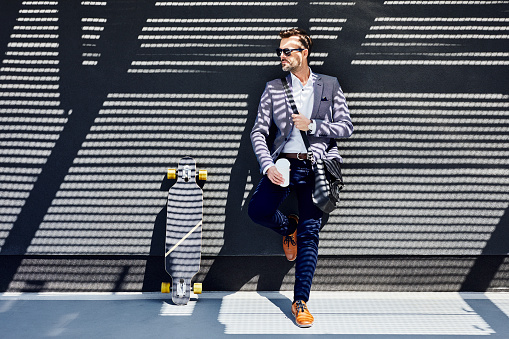Businessman with longboard and coffee leaning against wall - gettyimageskorea
