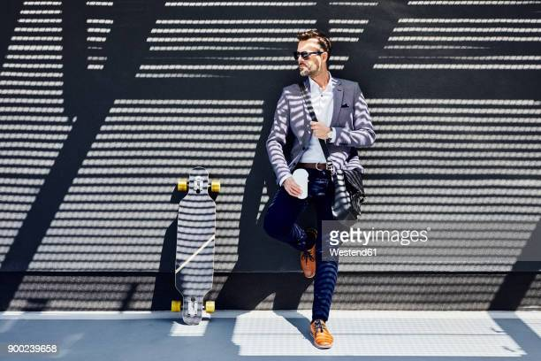 businessman with longboard and coffee leaning against wall - cool attitude stock pictures, royalty-free photos & images