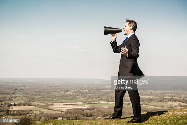 Businessman with loudhailer megaphone on hill