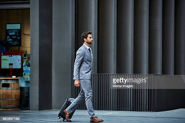 Businessman with luggage against building