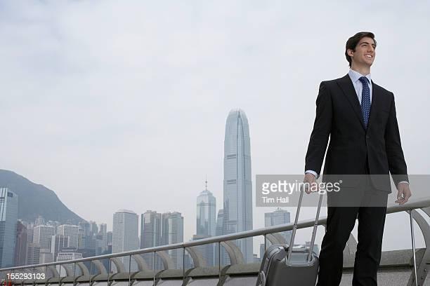 Businessman with luggage by urban bay