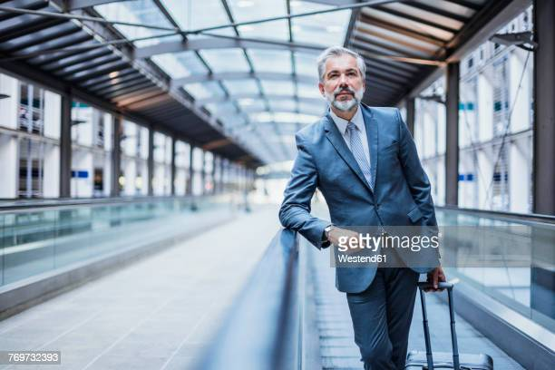 Businessman with luggage on moving walkway