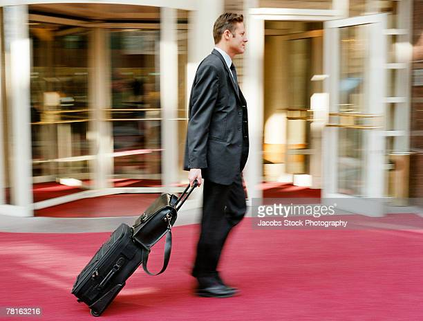 Businessman with luggage outside hotel