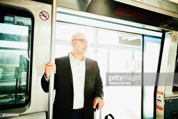 Businessman with luggage standing on commuter train