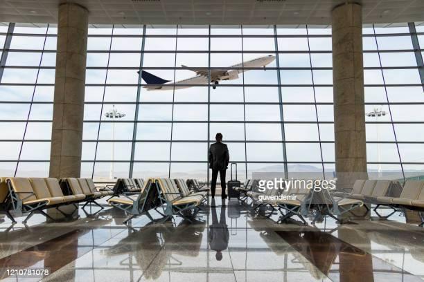zakenman met bagage die in de luchthaven wacht - luchthaven stockfoto's en -beelden