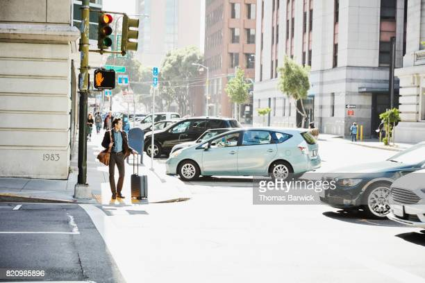 businessman with luggage waiting to cross city street - road signal stock pictures, royalty-free photos & images