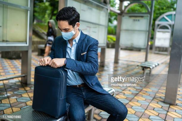 businessman with mask for air pollution sitting on bus station - virus organism stock pictures, royalty-free photos & images