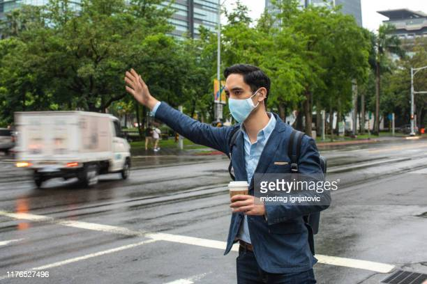 businessman with mask on his face hailing to taxi - waving stock pictures, royalty-free photos & images