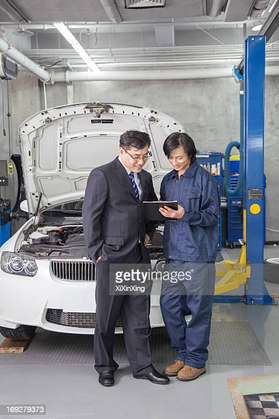 Businessman with Mechanic in Auto Repair Shop