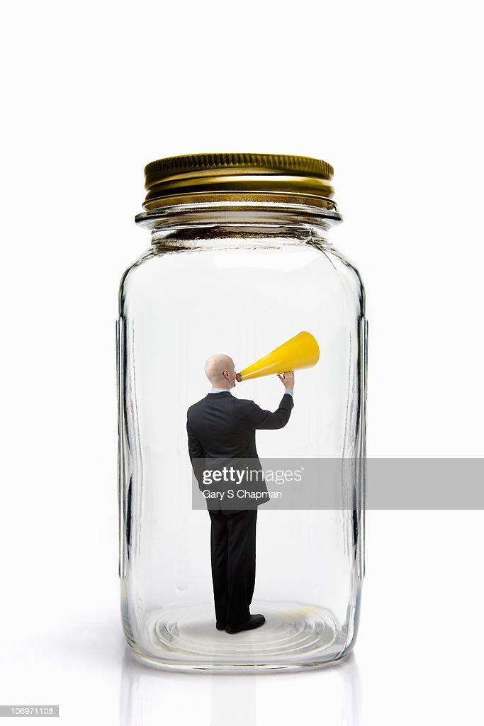 Businessman with megaphone inside mason jar. : Stock Photo