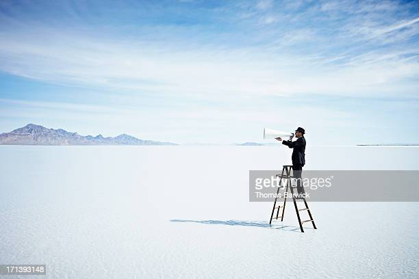 Businessman with megaphone on ladder in lake