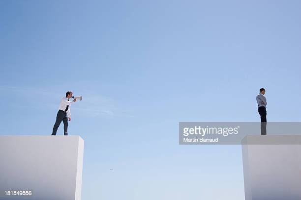 Businessman with megaphone on wall shouting at businessman on wall with gap
