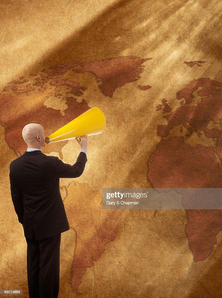 Businessman with megaphone speaking to world : Bildbanksbilder