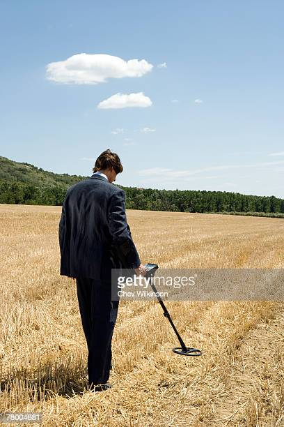 Businessman with metal detector outdoors.