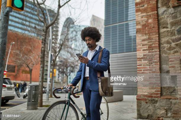 businessman with mobile phone and bicycle in city - mid adult men stock pictures, royalty-free photos & images