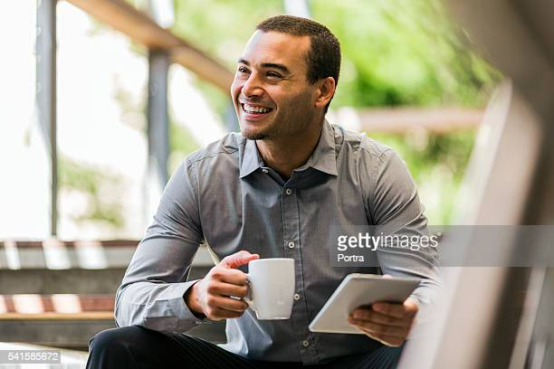 businessman with mug and digital tablet on steps - 30 39 years stock pictures, royalty-free photos & images