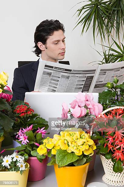 Homme d'affaires avec journal et plantes