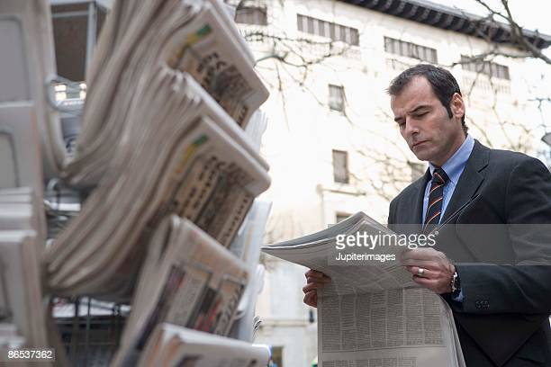 businessman with newspaper at newsstand - news stand stock pictures, royalty-free photos & images