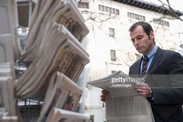 Businessman with newspaper at newsstand