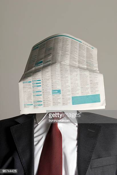 Businessman with newspaper covering face, Istanbul, Turkey