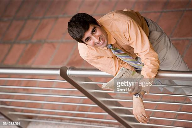 Businessman with Newspaper Leaning Against Railing