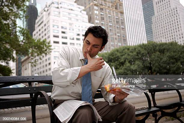 Businessman with newspaper on park bench, portrait, close-up