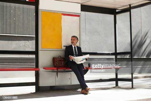 businessman with newspaper waiting at bus stop - sitting stock pictures, royalty-free photos & images