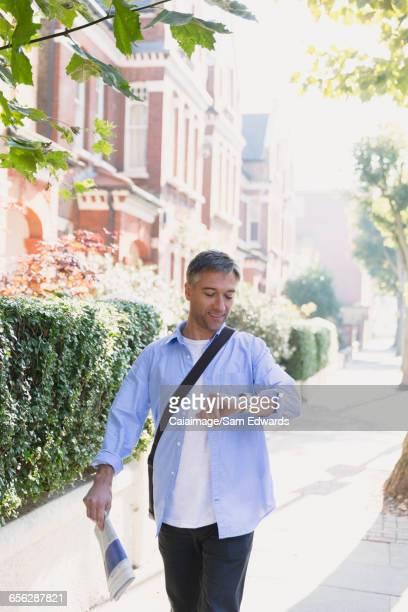 Businessman with newspaper walking on sidewalk and checking wristwatch