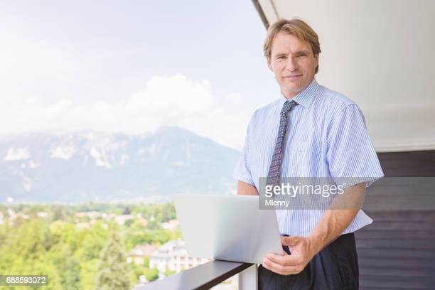 Businessman with notebook on balcony during business seminar break