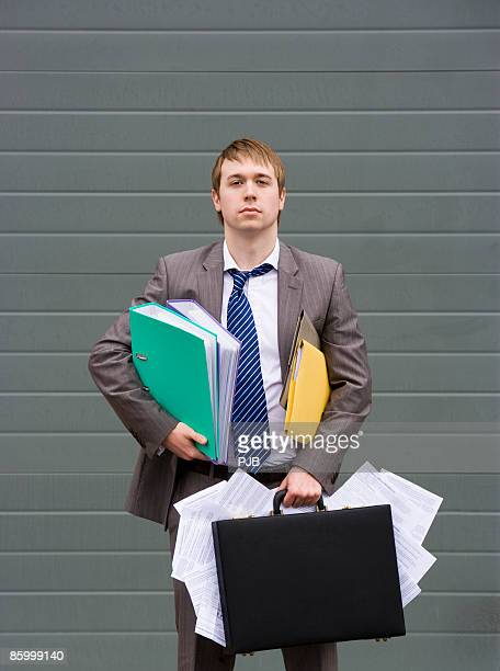Businessman with overstuffed briefcase and files