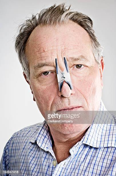 Businessman With Peg On His Nose.