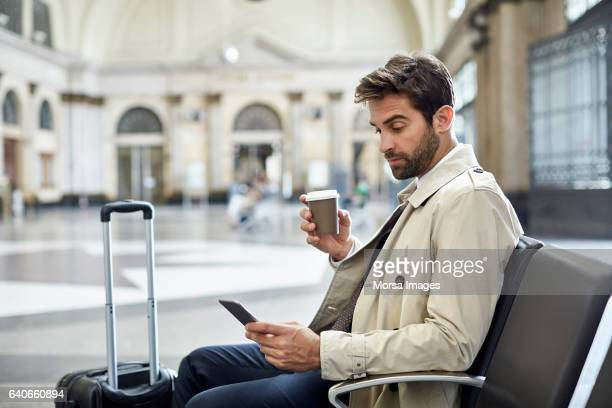 Businessman with phone and coffee at train station