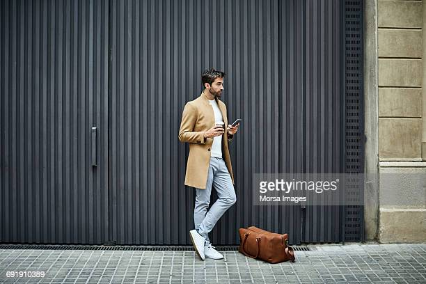 businessman with phone and cup looking away - coat stock pictures, royalty-free photos & images