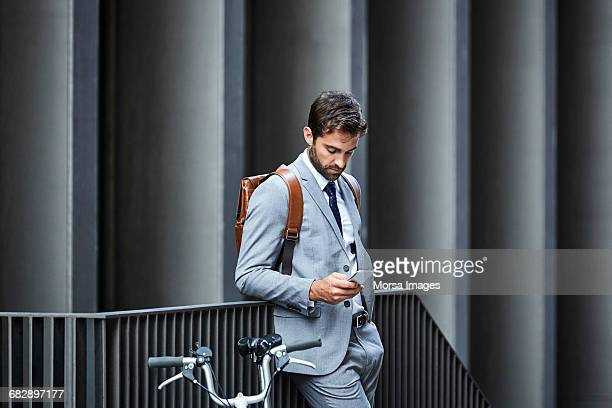 Businessman with phone and cycle by railings
