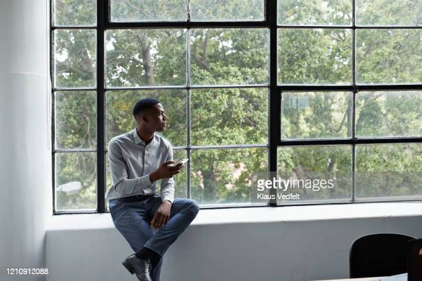 businessman with phone looking away at workplace - entrepreneur stock pictures, royalty-free photos & images