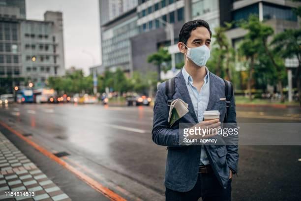homme d'affaires avec le masque de pollution restant sur la rue - masque de chirurgien photos et images de collection