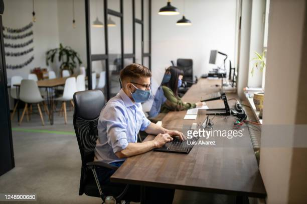 businessman with protective face mask working at his desk - coworking stock pictures, royalty-free photos & images