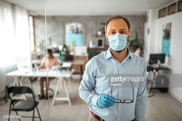 businessman with protective gloves and face mask at office - returning stock pictures, royalty-free photos & images
