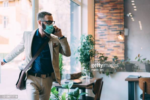 businessman with protective mask during covid-19 - entering stock pictures, royalty-free photos & images