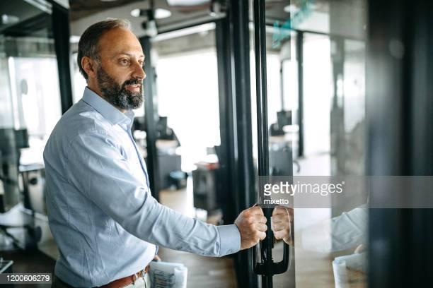 businessman with report at doorway in office - entrar imagens e fotografias de stock