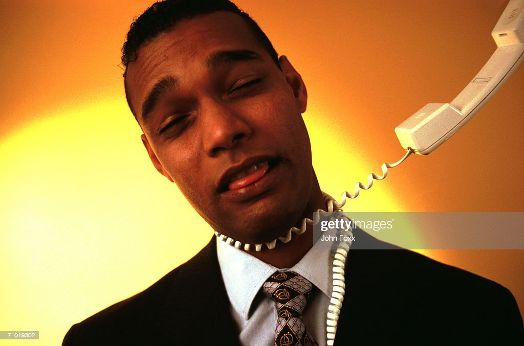 Businessman with rolled up telephone receiver around his neck : Stock Photo