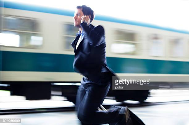 Businessman  with roller case Running For Train on Station Platform