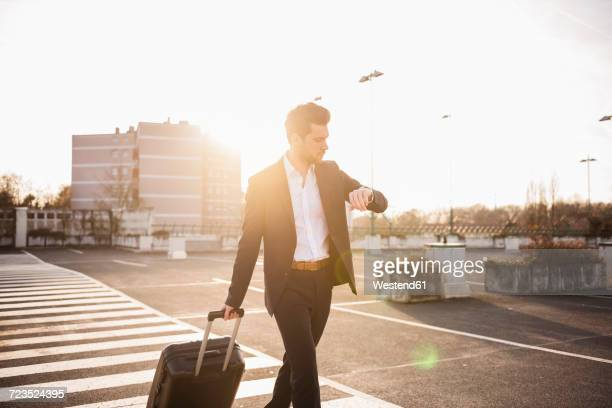businessman with rolling suitcase checking the time - geschäftsreise stock-fotos und bilder